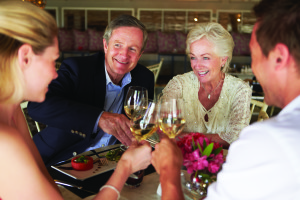 two couples toast with wine glasses at dinner table in restaurant
